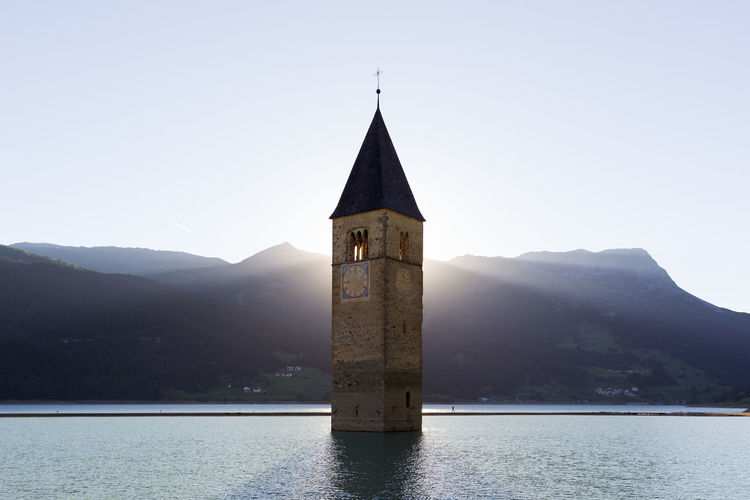 Bell tower in sea against mountains
