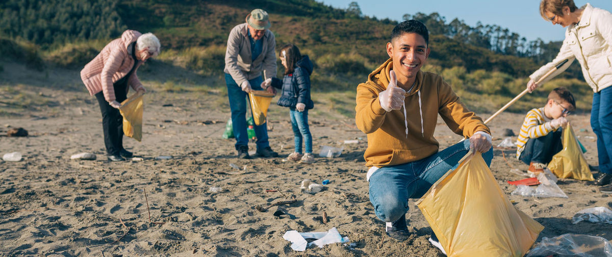 Family picking garbage while cleaning beach