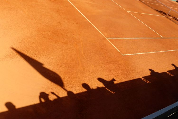 High angle view of people shadow on tennis field