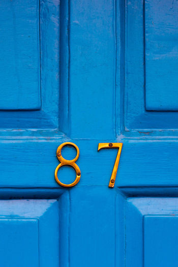 House number 87 on a blue wooden front door in london