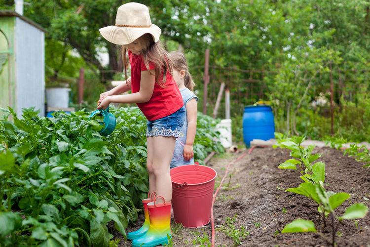Full length of girl wearing hat in yard