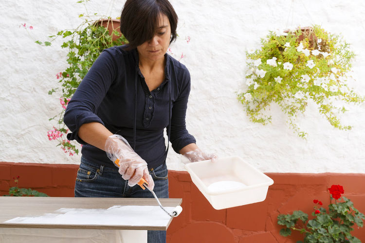 woman paint in beautiful backyard Decorating Roller Renovation Casual DIY Female Paintbrush Domestic Happy Traditional House Exterior Woman Paint Restore Maintenance Painting One Person Real People Lifestyles Plant