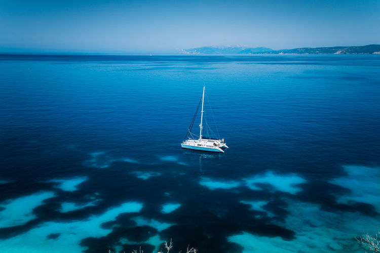 High angle view of sailboat sailing in sea against sky