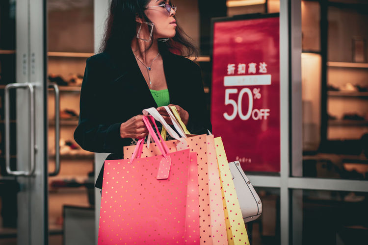Midsection of woman standing by store
