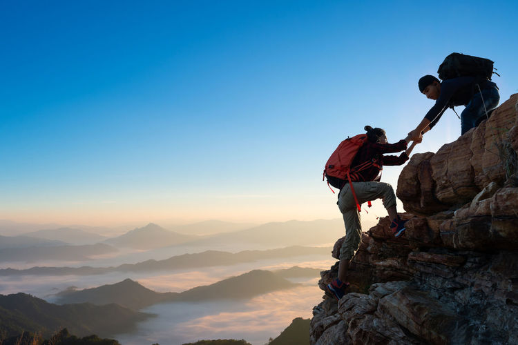 Asia couple hiking help each other on mountains view . teamwork