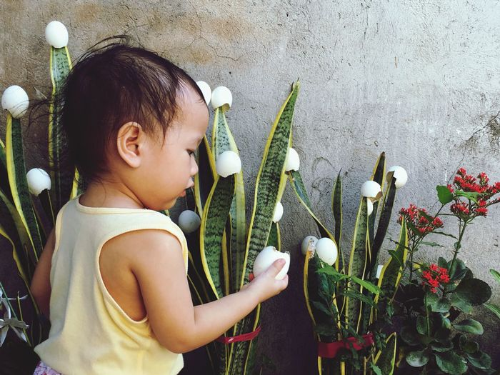 Side view of cute girl holding egg shell by flowering plants
