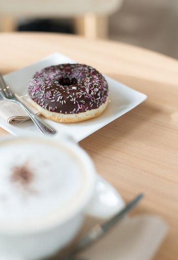 Close-up of donut with fork in plate on table