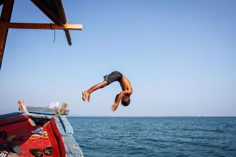 Man jumping from boat into sea against clear sky