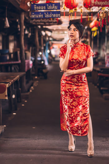 Thoughtful woman in red dress standing at market