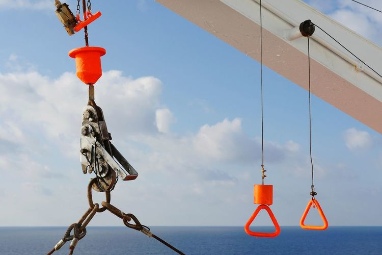 Low angle view of boat equipment hanging by sea against sky