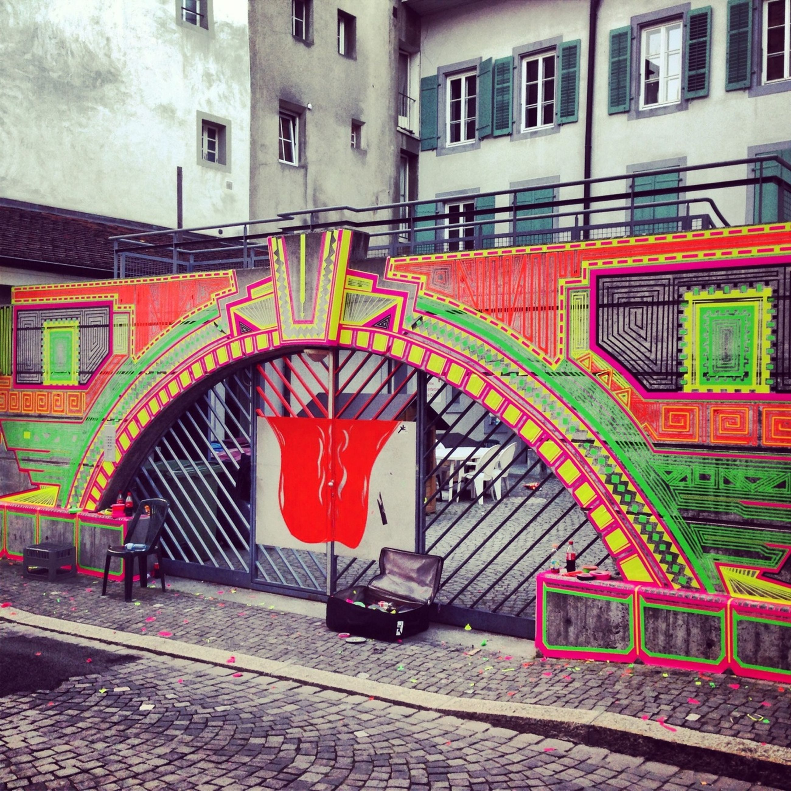 architecture, built structure, building exterior, arch, red, multi colored, graffiti, city, art and craft, building, art, cobblestone, day, street, outdoors, railing, wall - building feature, creativity, entrance, steps