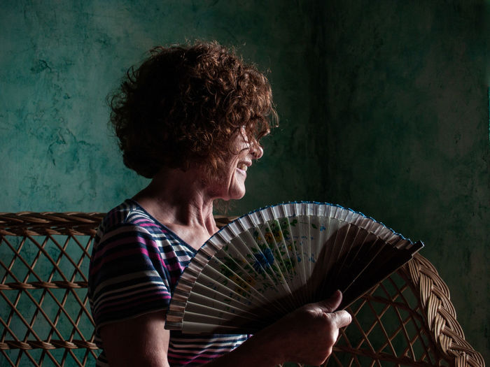 Woman looking away while holding hand fan
