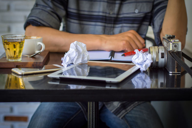 Midsection Of Man Sitting With Tablet And Crushed Papers On Table