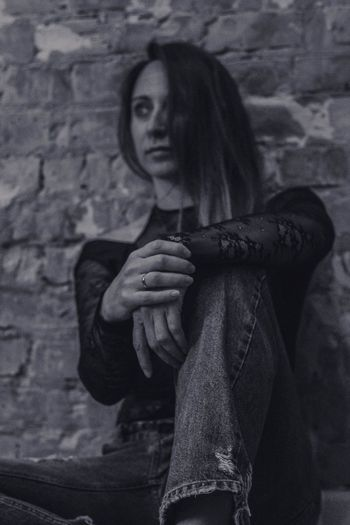 Low Angle View Of Thoughtful Young Woman Sitting Against Wall