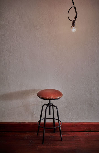 Low angle view of illuminated lamp on table against wall