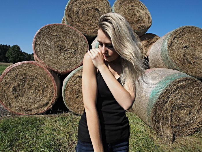 Young woman standing against hay bales on field during sunny day