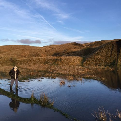 Person standing in shallow water by hill against sky