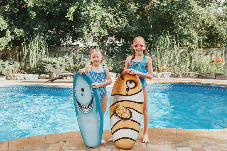 Portrait of smiling girls by swimming pool