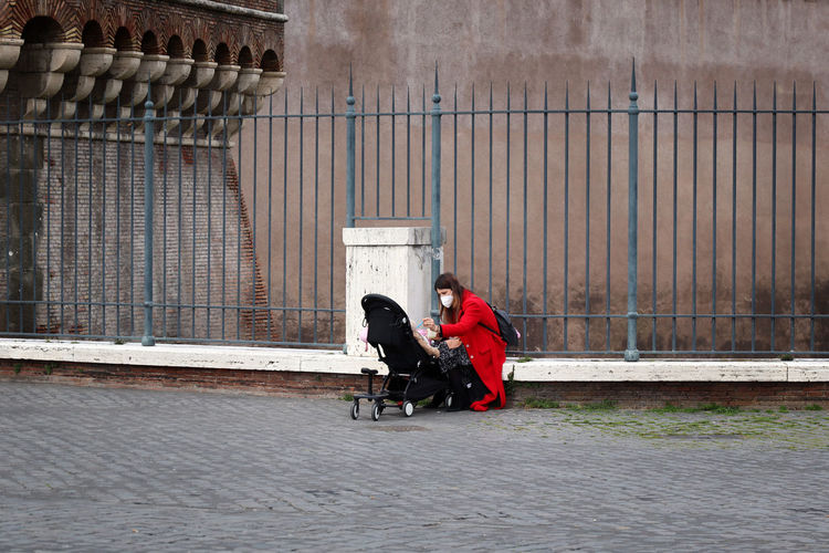 Side view of man and woman sitting on footpath