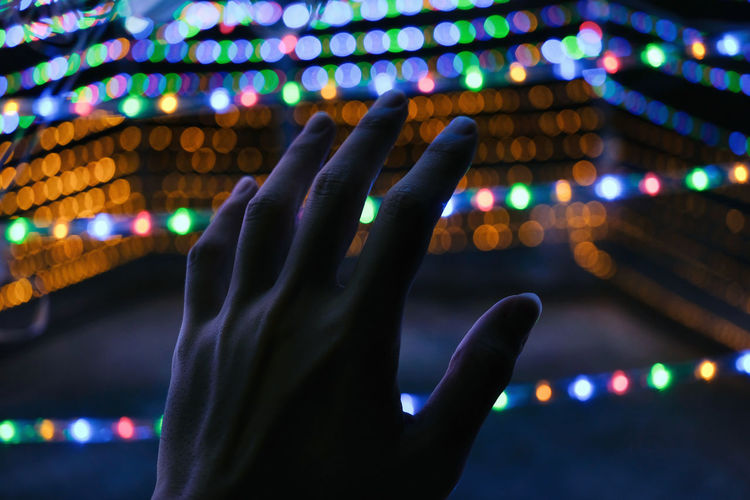 Cropped hand against illuminated lights at night