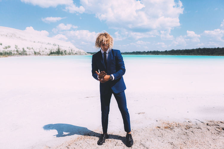 Blond curly guy dressed in business suit is posing on the crystal clear lake. Trendy hairstyle, awesome shoot. Summer time. Beach Beauty In Nature Casual Clothing Cloud - Sky Day Full Length Hair Hairstyle Land Leisure Activity Lifestyles Nature One Person Outdoors Real People Scenics - Nature Sky Standing Water Young Adult