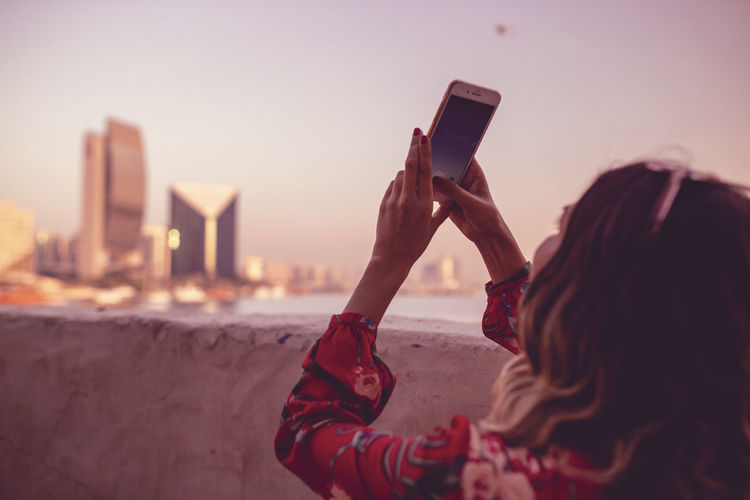 Close-Up Of Young Woman Taking Picture On Mobile Phone Against Sky