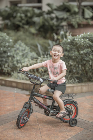 Just one happy kid on a lazy afternoon. Bicycle Casual Clothing Child Childhood Day Emotion Full Length Happiness Leisure Activity Lifestyles Looking At Camera One Person Outdoors Real People Riding Sitting Smiling Transportation Women Summer In The City