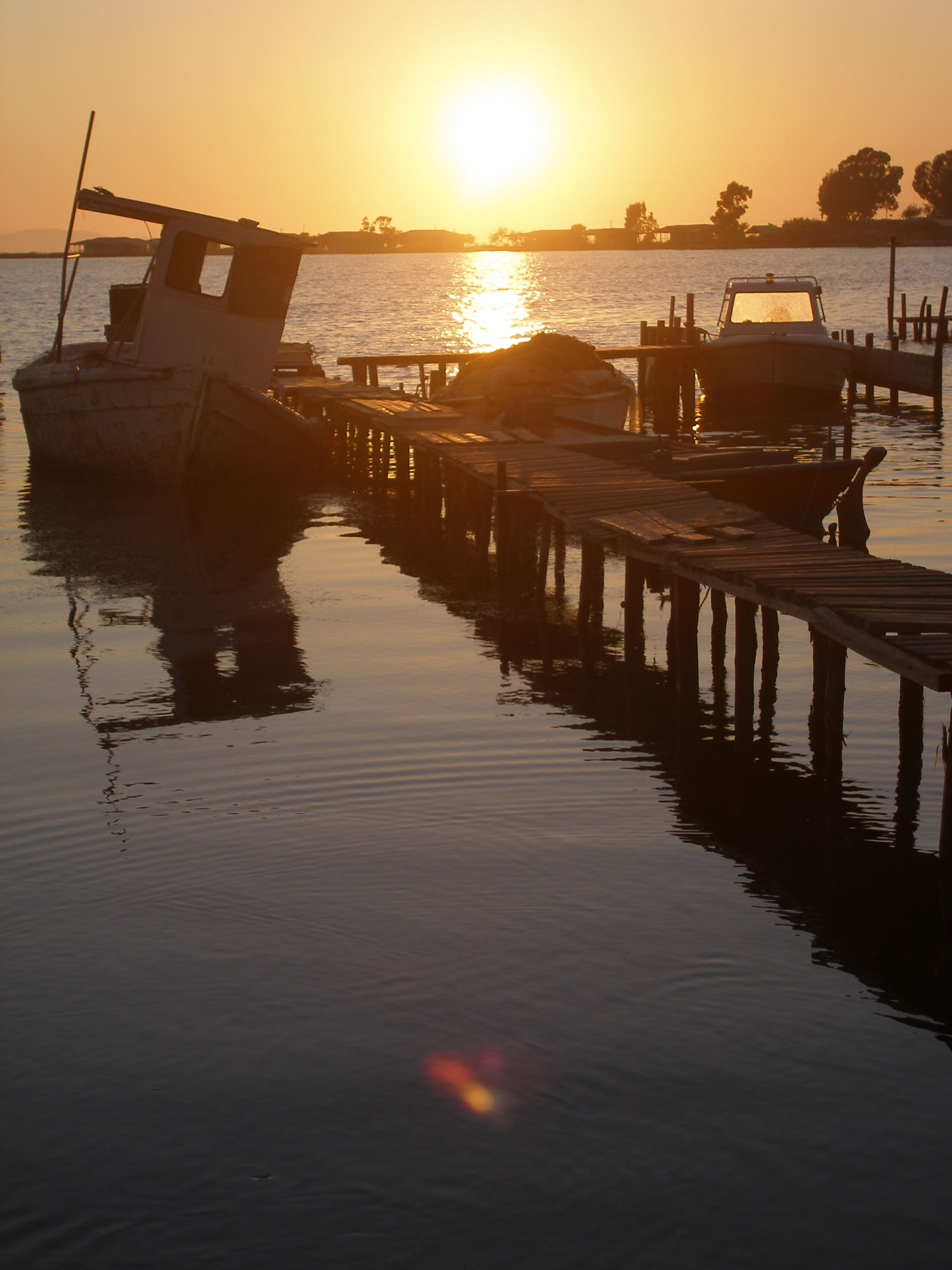 water, sunset, sea, sun, reflection, pier, orange color, silhouette, tranquil scene, tranquility, sunlight, horizon over water, scenics, sky, built structure, beauty in nature, waterfront, nature, rippled, idyllic