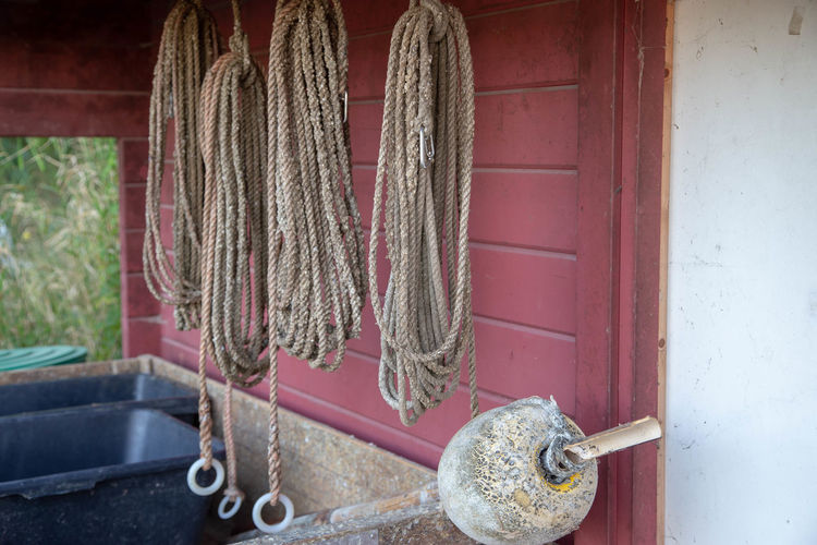 Close-up of rope tied on metal against wall