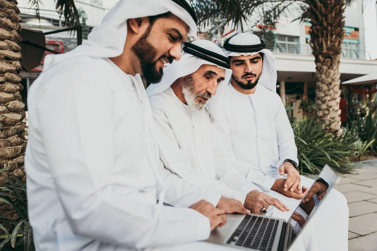 Senior man with grandsons wearing dish dash using laptop outdoors