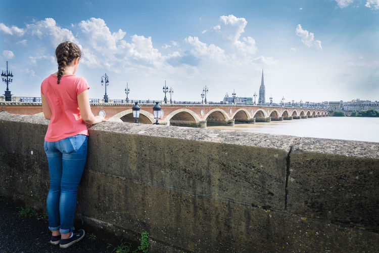 Girl looking at the city across the river Alone Beautiful Beauty Bordeaux Bridge City Cityscape Connecting Crossing Female Longing Missing Rear View River Riverside Street Travel
