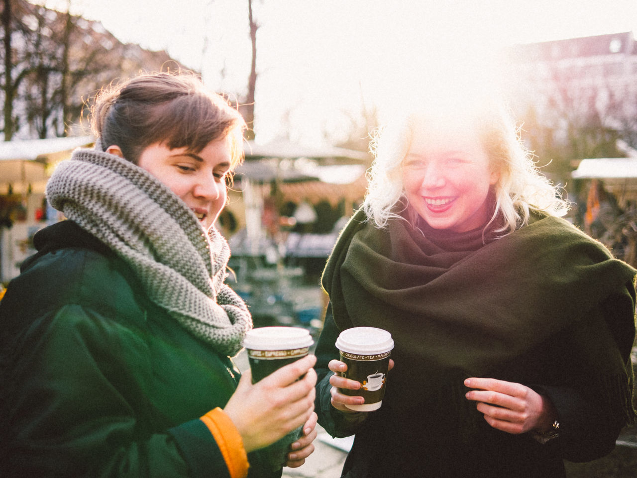 Happy friends holding disposable coffee cup in flea market