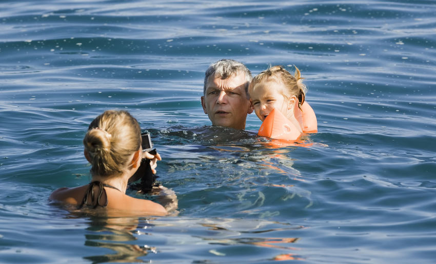 Portrait of mother and girl swimming in water