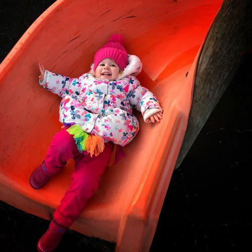 Portrait of smiling girl lying on slide