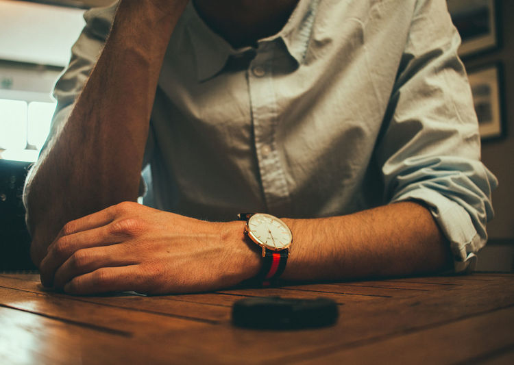 Accessory details EyeEm Best Shots The Week on EyeEm Accuracy Button Down Shirt Clock Focus On Foreground Front View Hand Human Hand Indoors  Lifestyles Men Midsection One Person Real People Table Time Watch Wood - Material Working Wristwatch