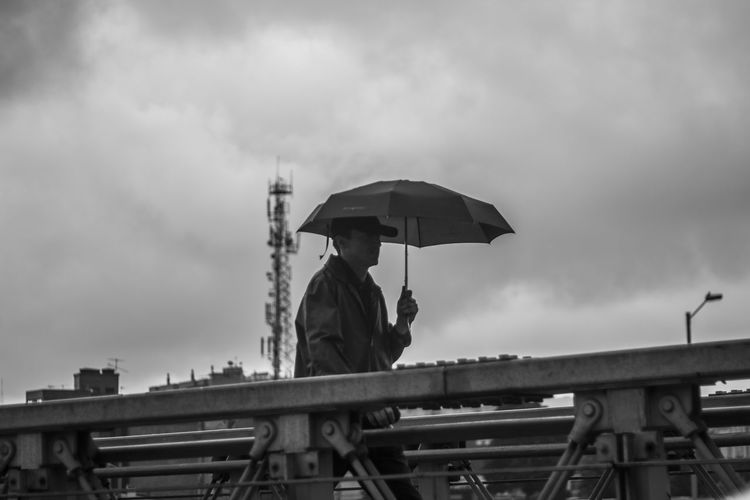 Low angle view of man with umbrella against sky
