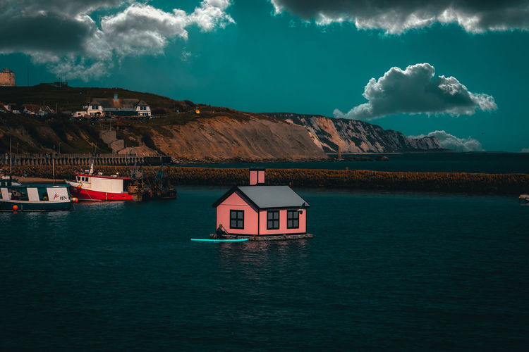 Scenic view of sea and houses against sky