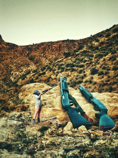 Woman aiming gun by sculptures while standing on mountain
