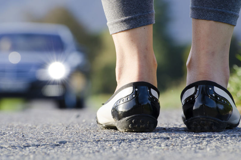 Woman Standing on the Road and a Car Asphalt Light Low Angle View Shoe Sunny Traffic Transportation Ballarina Car Close-up Day Focus On Foreground Human Body Part Human Leg Low Section Motion On The Move One Person One Woman Only Outdoors People Real People Standing Women