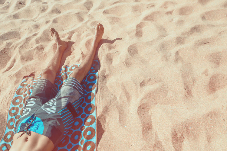 Low Section Of Man Resting On Patterned Towel At Beach