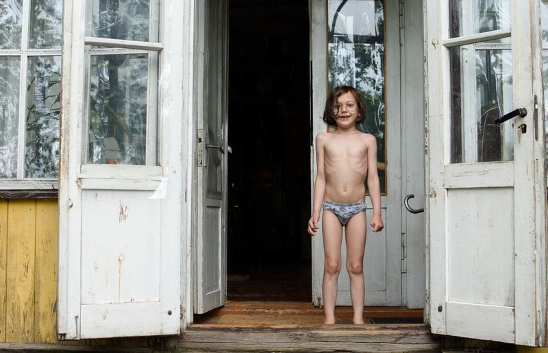 Portrait of shirtless boy standing at doorway