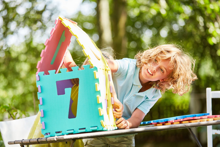 portrait of smiling woman holding umbrella Assemble Blond Hair Boy Build Building Construction Casual Clothing Child Childhood Children Colorful Construction Creative Creativity Day Dream House Emotion Focus On Foreground Front View Fun Future Game Hair Hairstyle Holding Home House Idea Jigsaw  Jigsaw Piece Jigsaw Puzzle Kids Leisure Leisure Activity Lifestyle Lifestyles Miniature Model Nature Numbered Numbers One Person Outdoors Outside Part Play Portrait Puzzle  Puzzle Piece Real Estate Real People Smiling Summer Together Vision Women