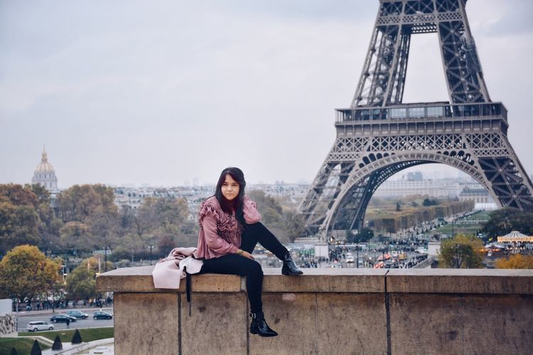 Portrait of young woman sitting against eiffel tower