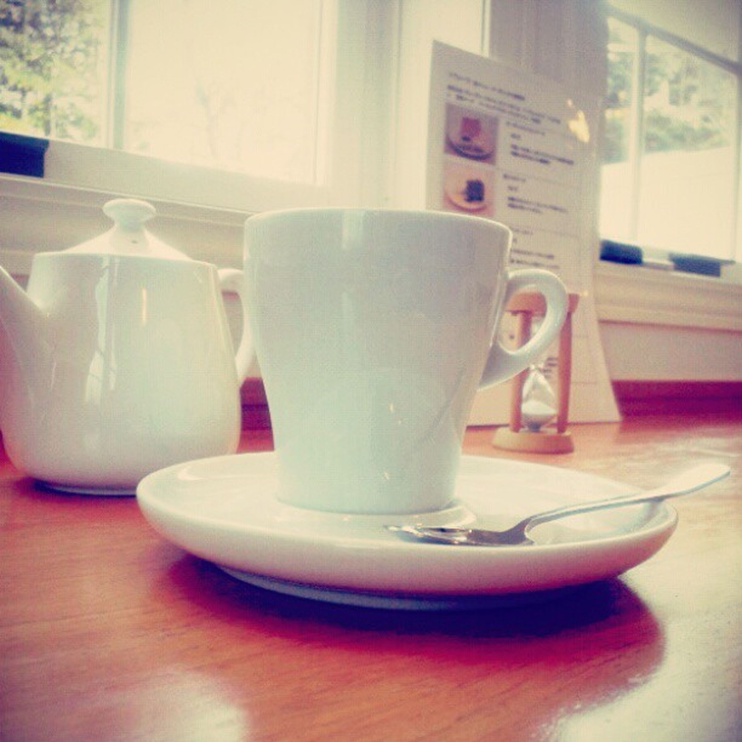 indoors, table, drink, still life, refreshment, close-up, coffee cup, food and drink, empty, focus on foreground, no people, glass - material, home interior, absence, selective focus, book, communication, cup, text, coffee