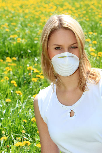 young woman protects herself with a respiratory mask against pollen allergy Nature Woman Adult Allergy Blond Hair Day Girl Illness Lifestyles Looking At Camera Mask Nature One Person Outdoors Painful People Pollen On Flowers Portrait Protection Respiratory Mask Sick Sickness Springtime Summer Young Women