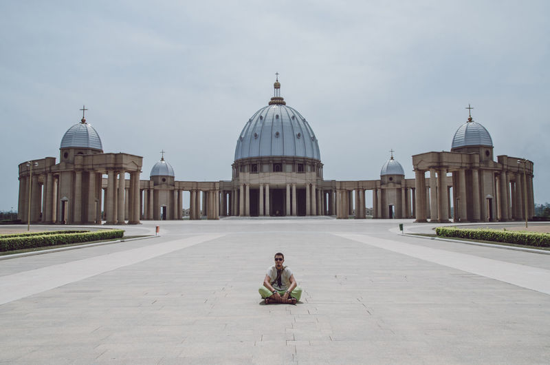 Tourist Tourist Attraction  Africa Architectural Column Architecture Belief Building Exterior Built Structure Côte D'ivoire Day Dome Full Length Ivory Coast Lifestyles One Person Place Of Worship Real People Religion Sitting Sky Spirituality Tourism Tourist Destination Travel Travel Destinations