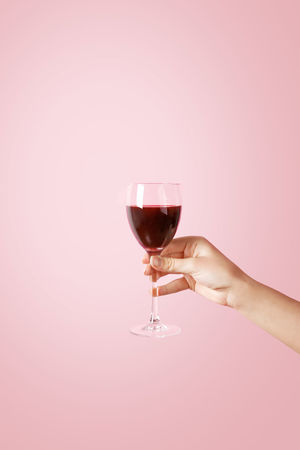 Hand holding a wine glass on pastel background Background Caucasian Clean Concept Female Glass Hand Hold Holding Pastel Pastel Background Pink Pink Background Red Wine Simple Wine Wine Glass Woman