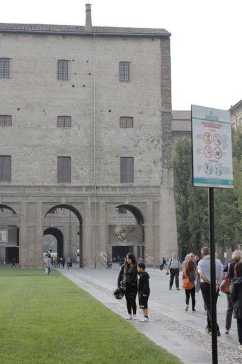 People walking on building against clear sky