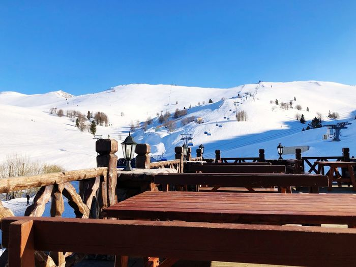 Sky Mountain Nature Water Railing Beauty In Nature Day Scenics - Nature Architecture Land Blue Sea Outdoors Built Structure Mountain Range Sunlight Snow Wood - Material Snowcapped Mountain Pier