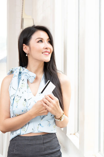 Smiling young woman looking away while holding credit card by window